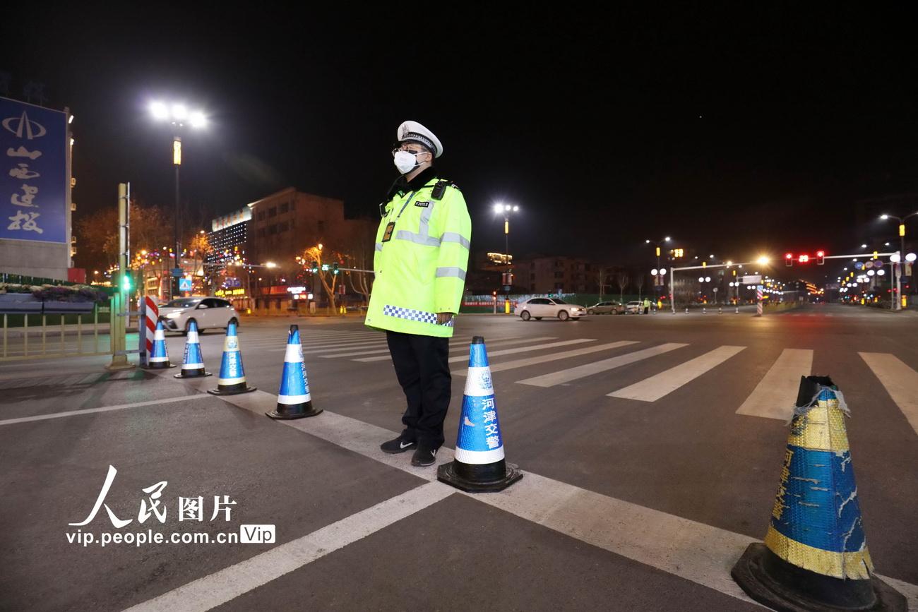 2月12日,齐胜波在市区繁华路段防疫检查点进行交通管控。