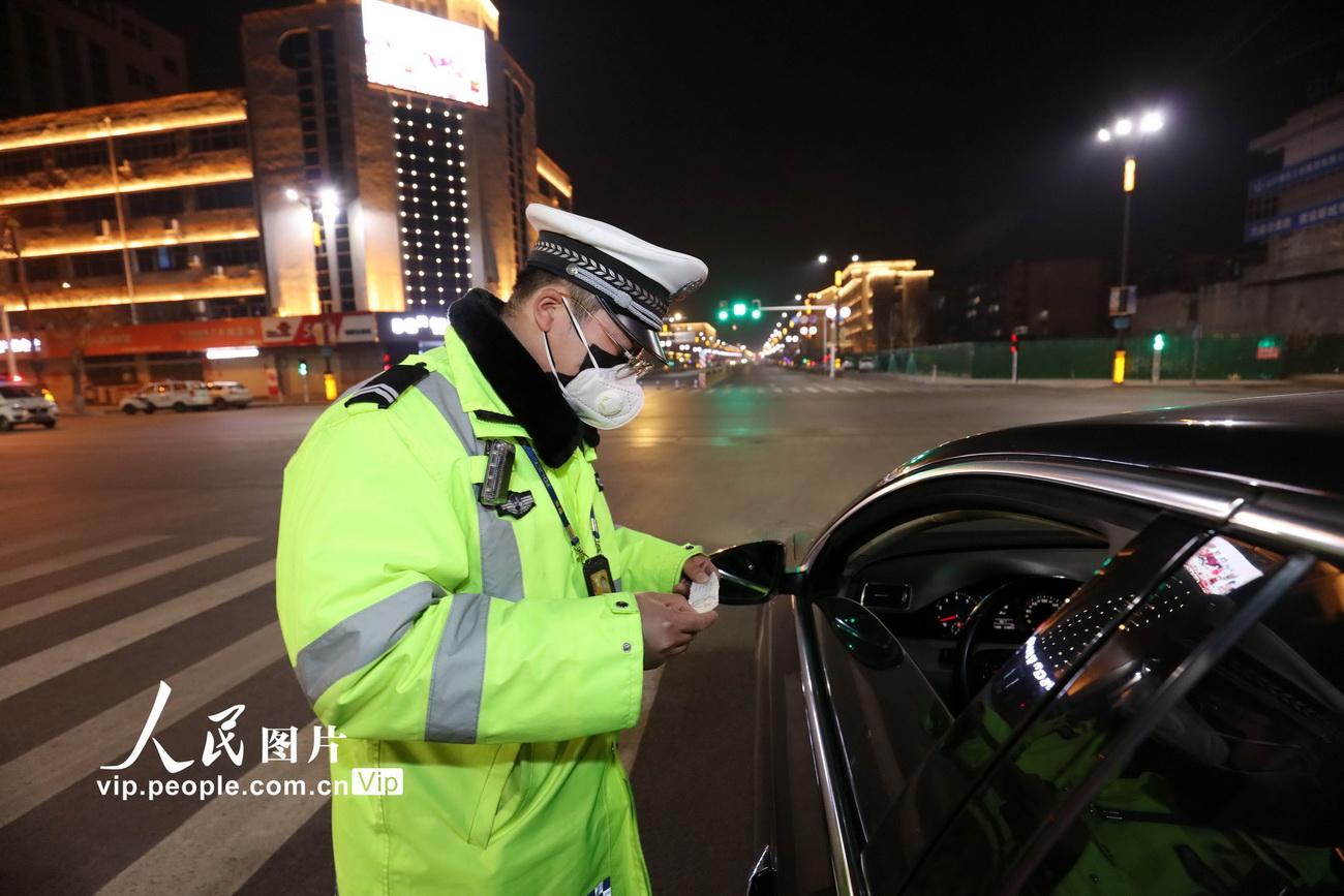 2月12日,齐胜波在市区繁华路段防疫检查点,检查车辆通行证。